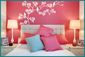 Bedroom with a pastel red feature wall behind the beds headboard