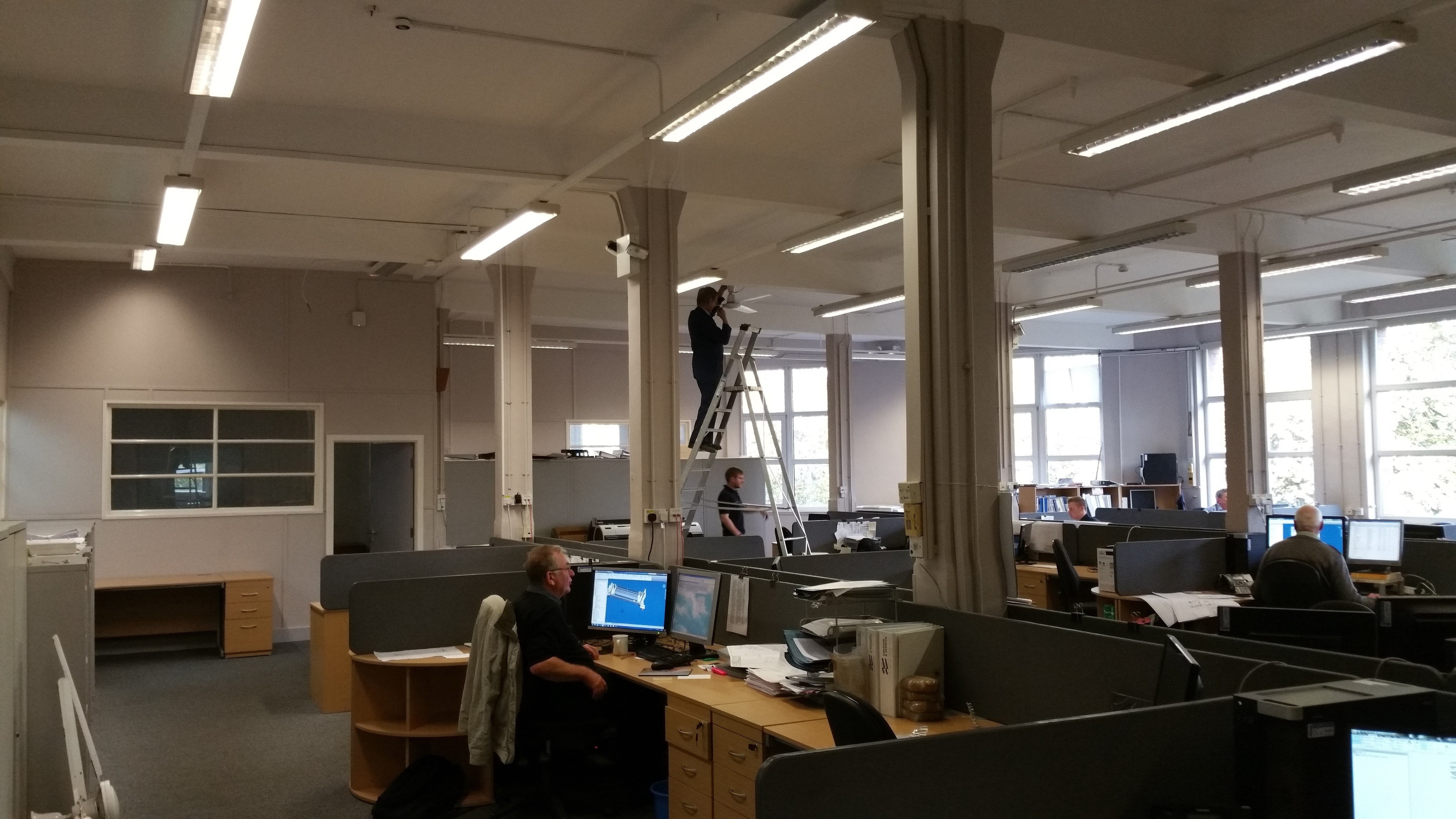 A man on a step ladder, installing suspended ceiling lights