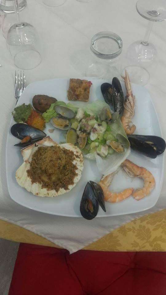 un piatto con capesante gratinate,cozze,gamberi e altro pesce