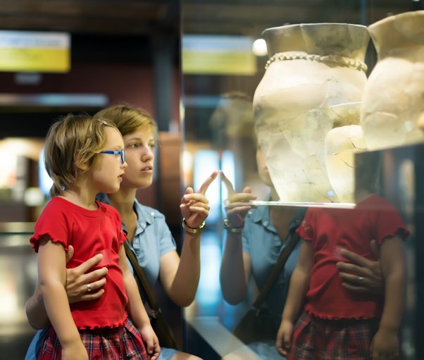 A lady pointing out a museum exhibit to a child