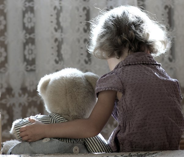 A young girl holding a large teddy bear