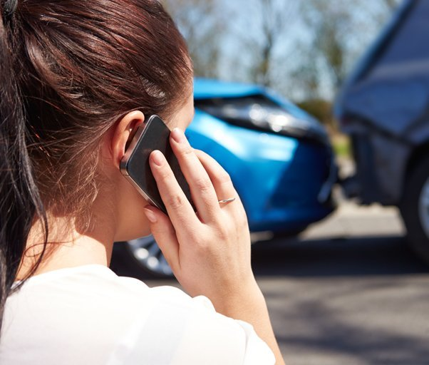 A lady on a phone with bumped cars in the background