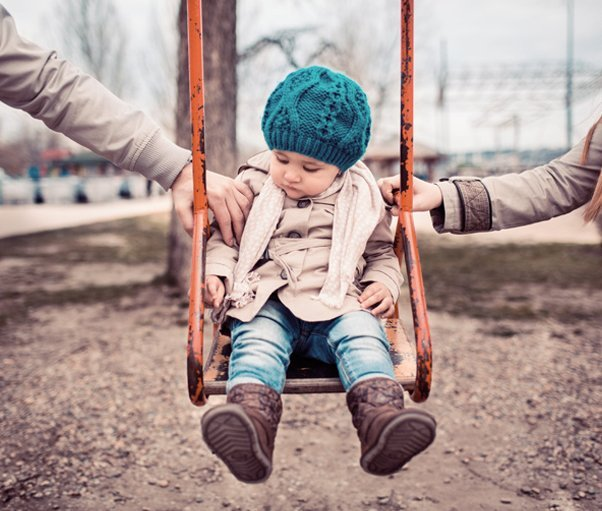 A young child being pushed on a swing by a man and a woman