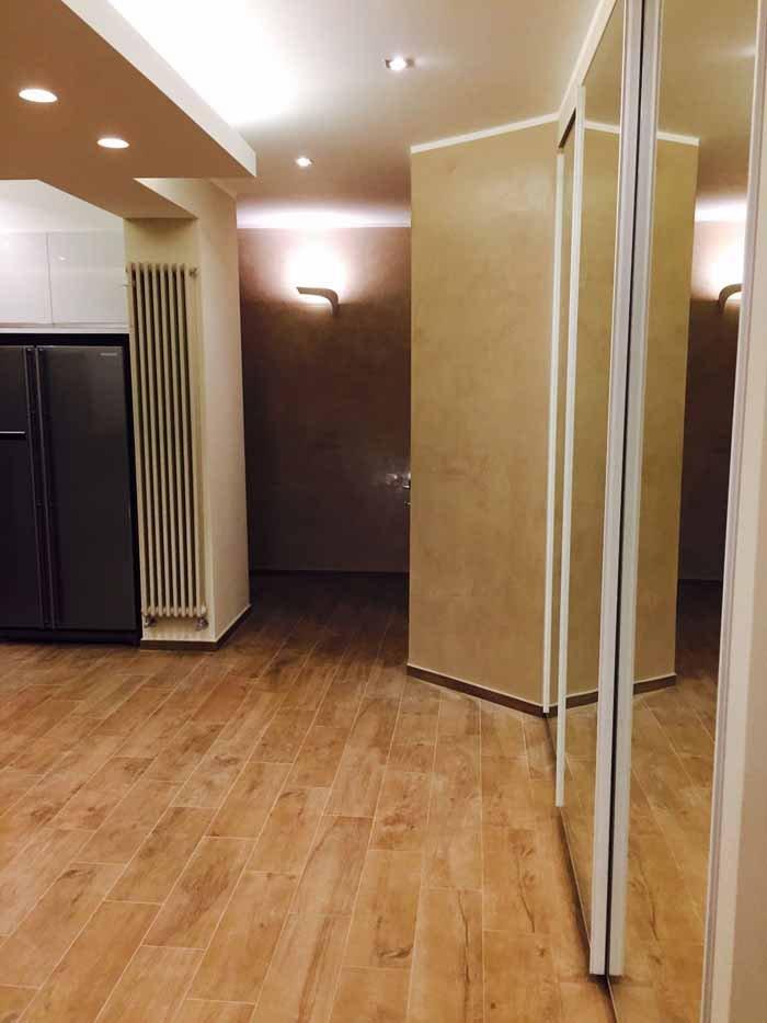parte di una stanza con frigorifero termosifone e armadio a specchio
