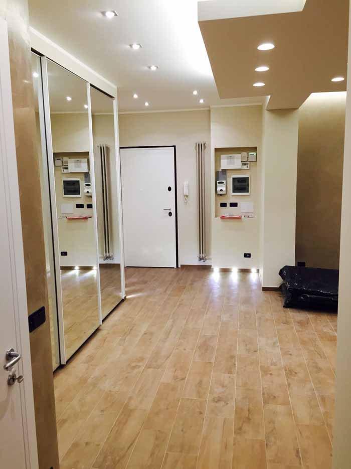 vista della porta d`entrata di un appartamento con armadio a  specchio scorrevole