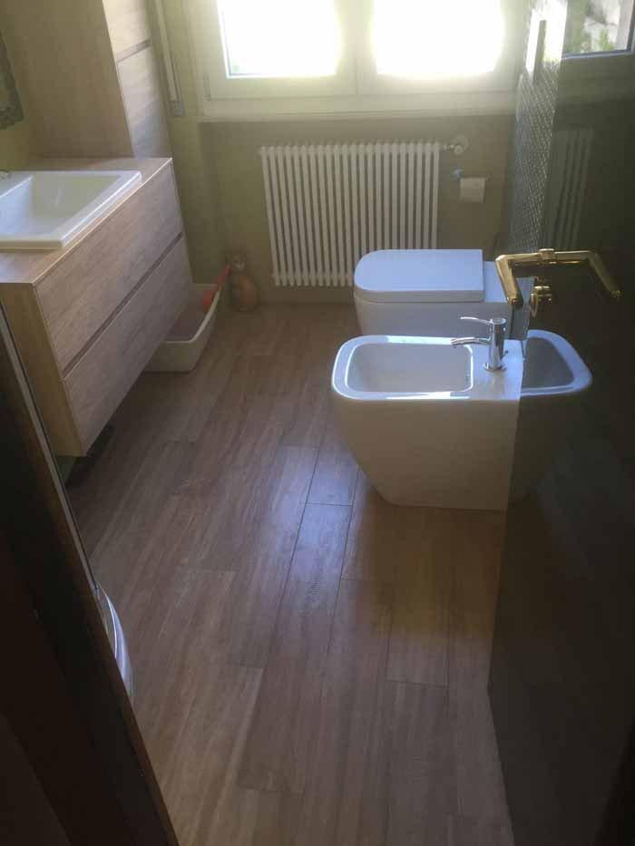 vista di un bagno con pavimento in legno, lavabo e bide