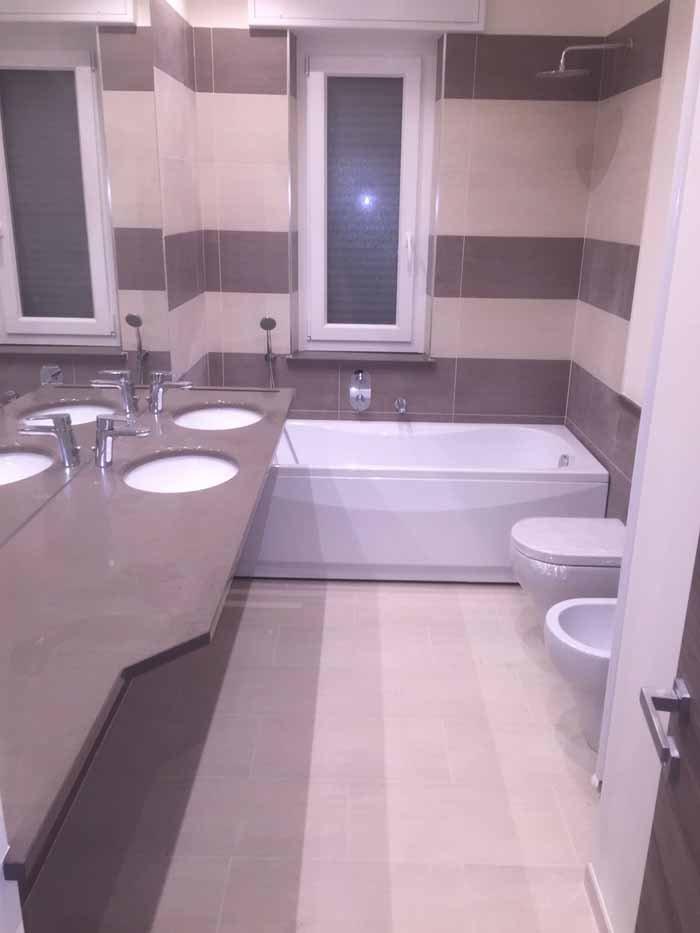 vista interna di una bagno con bancone di lavabi, vasca e bide