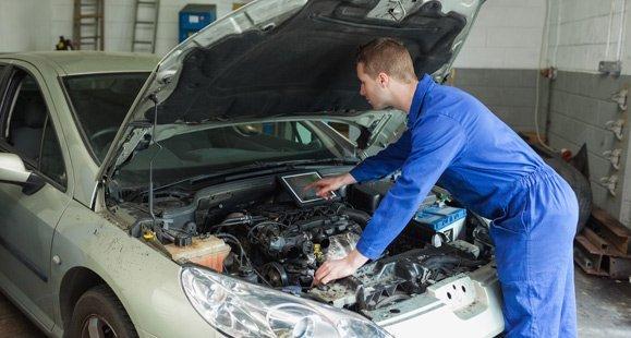 masons budget tyres mechanic examining car engine