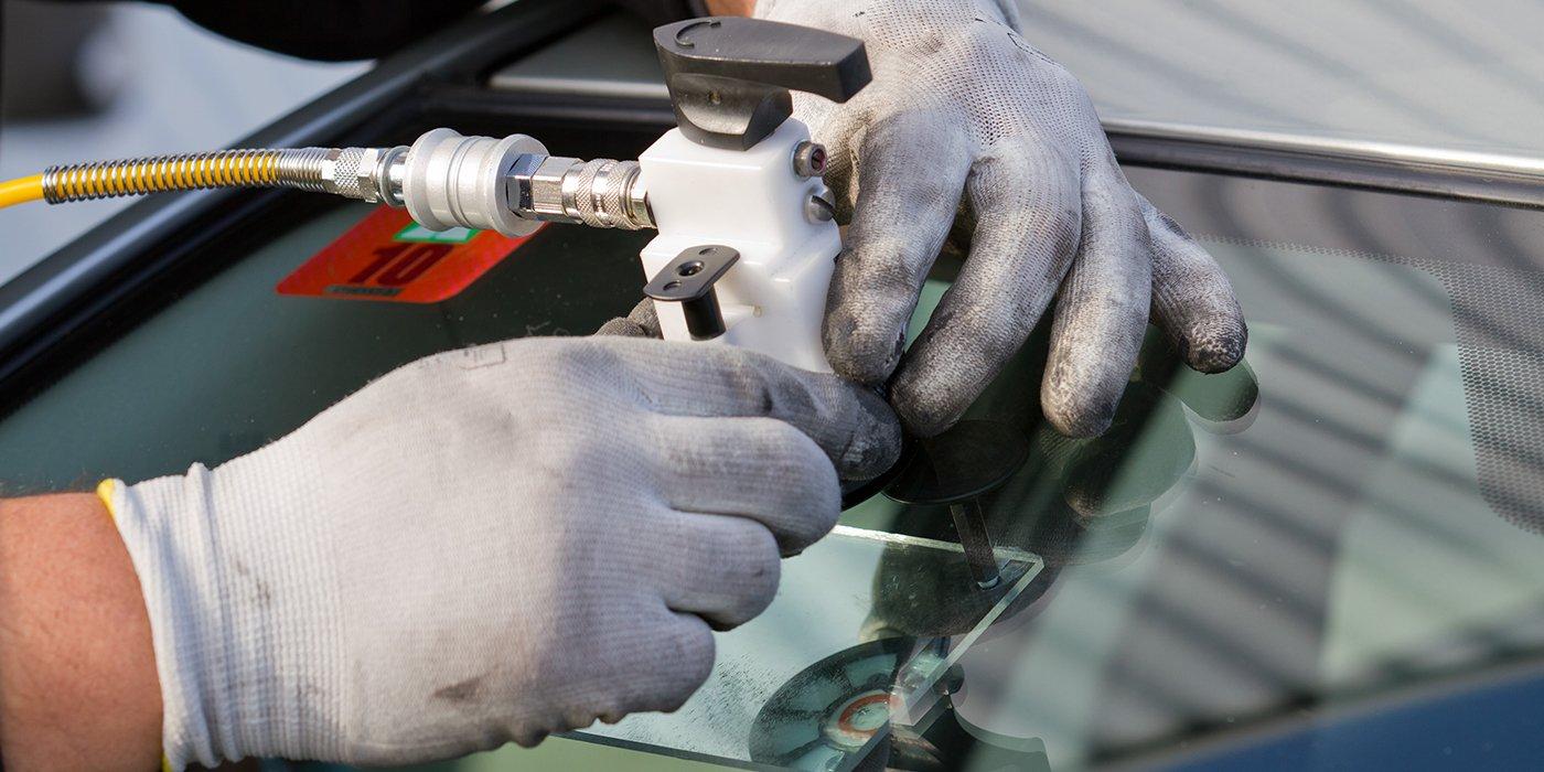 due mani con de guanti che applicano un dispositivo a ventosa sul vetro anteriore di una macchina