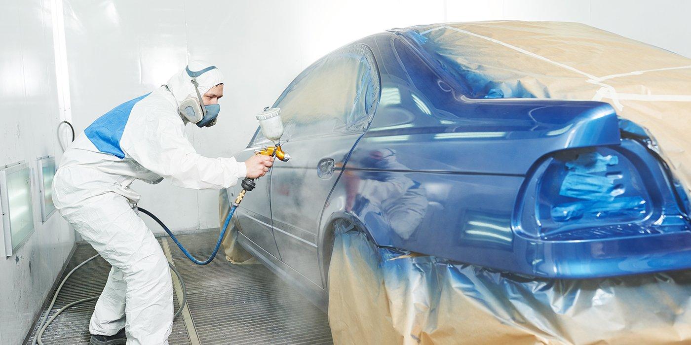 un uomo con una tuta protettiva mentre vernicia una macchina