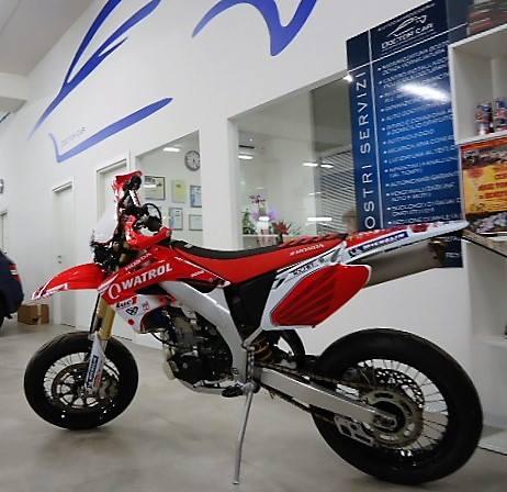 una moto da cross color rosso e bianco vista da un'angolazione diversa