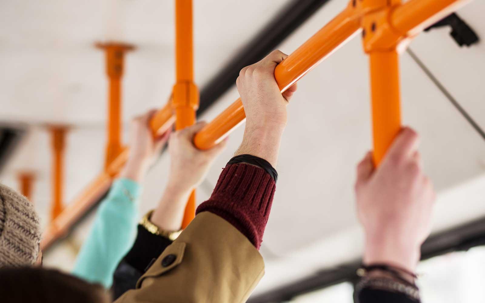 Persone aggrappate nella barra di un autobus