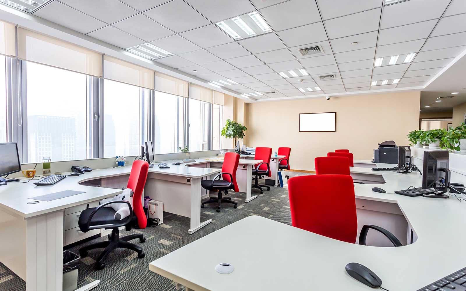 Interno di un ufficio con mobili bianchi e sedie rosse