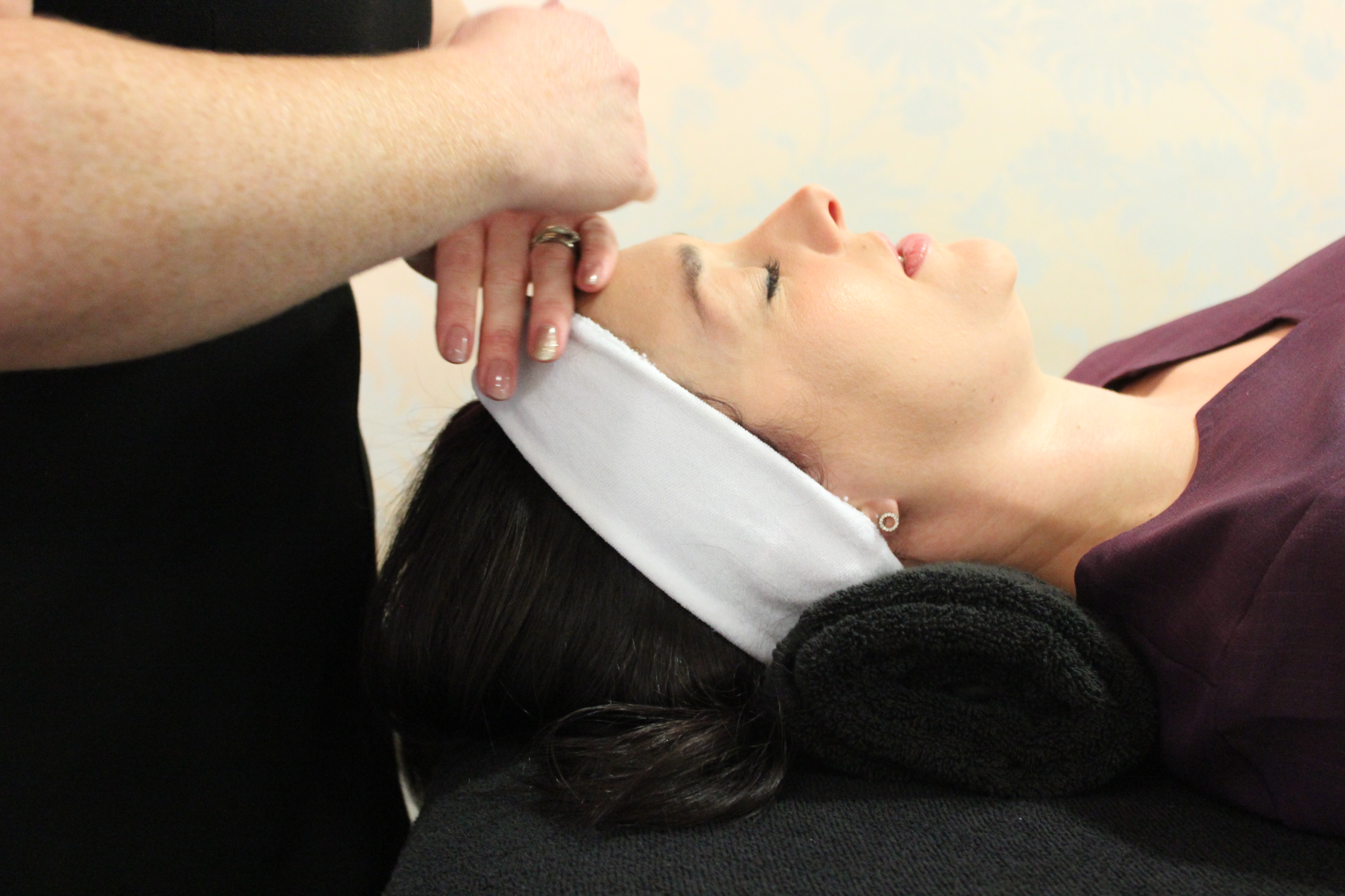Close up image of a woman with dark hair receiving a massage before a facial treatment