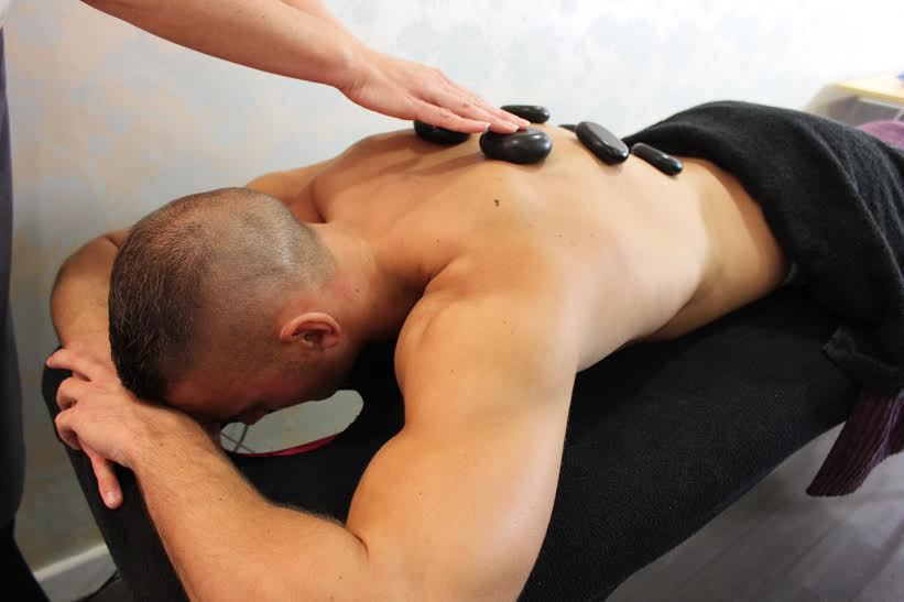 Mid angle shot of a man receiving a hot stone massage