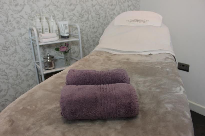 High angle shot of a massage table covered in a grey material with two folded purple towels
