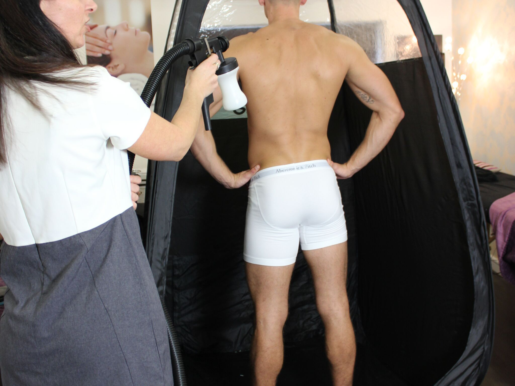 Photograph of a man receiving a spray tan
