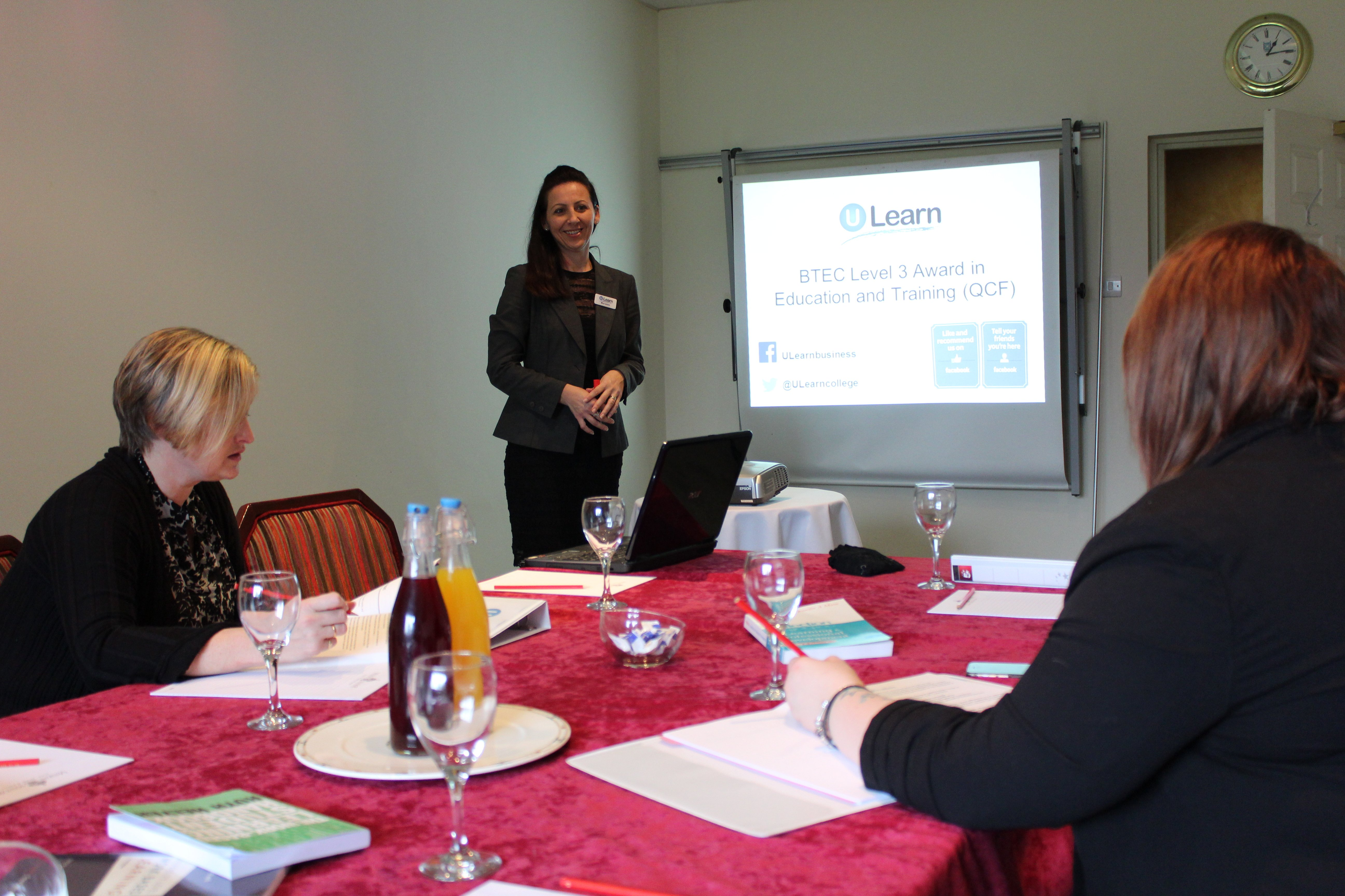 Image of a smartly dressed woman delivering a presentation to  a room of several people