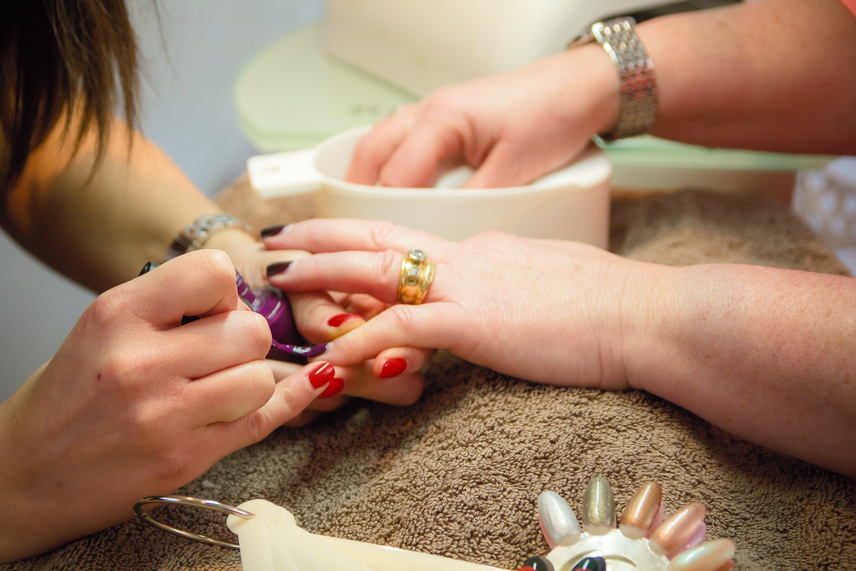 Close up of two women's hands, one applying a manicure to the other