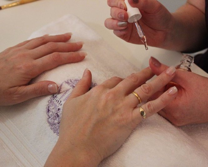 Close up shot of the hands of two women, one giving the other a manicure