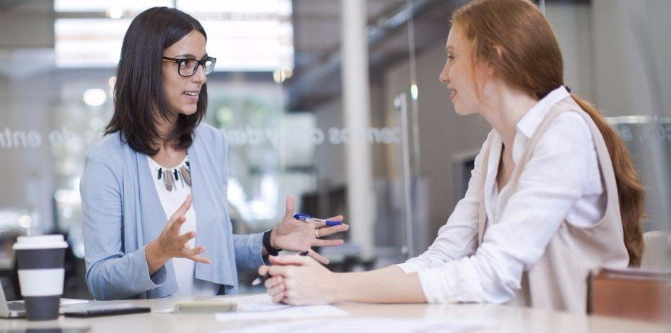 Two women in business clothing having a discussion