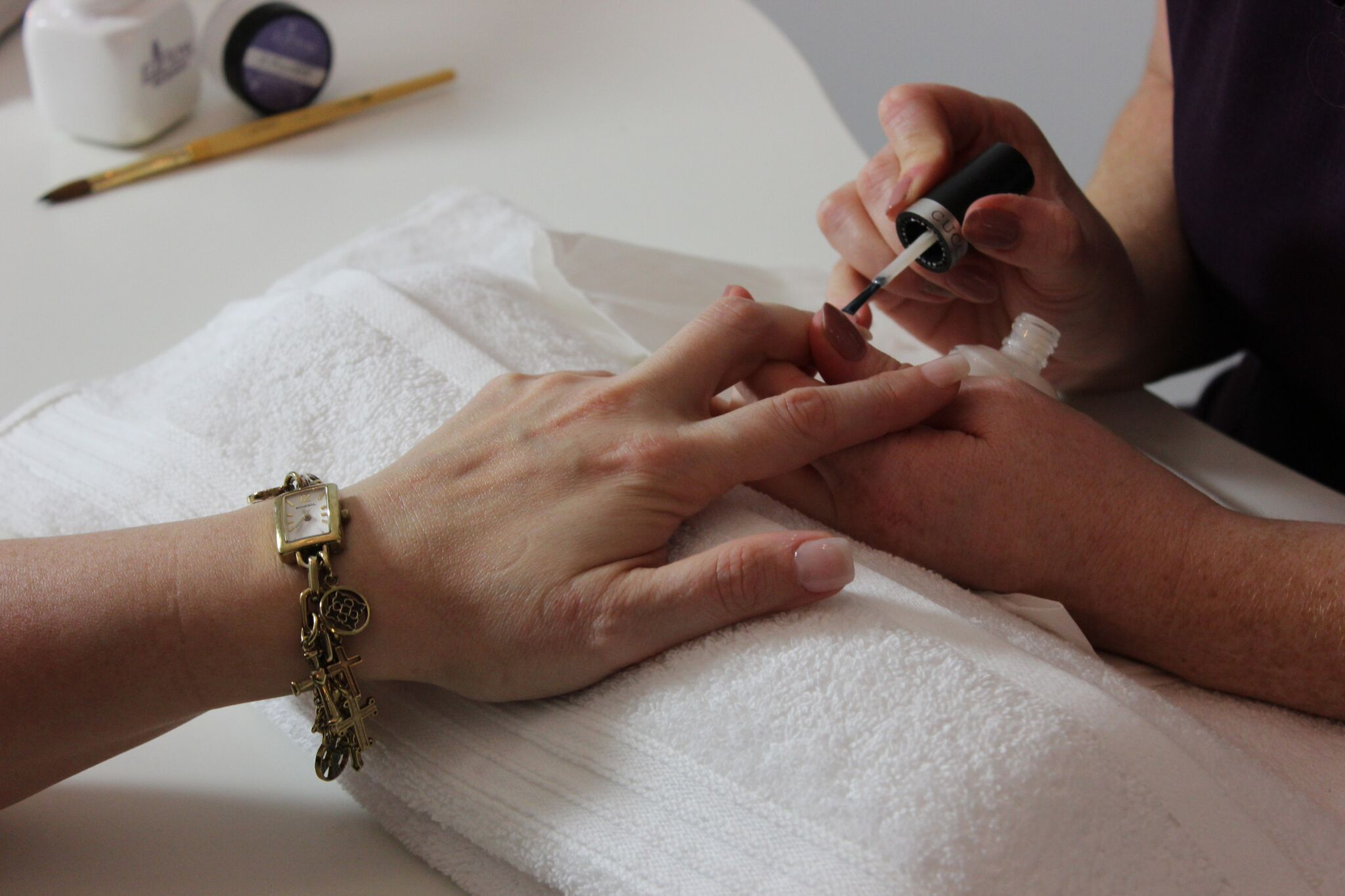 Close up image of the hand of a woman who is receiving a manicure