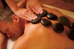 High-angle image of a man receiving a hot stone massage