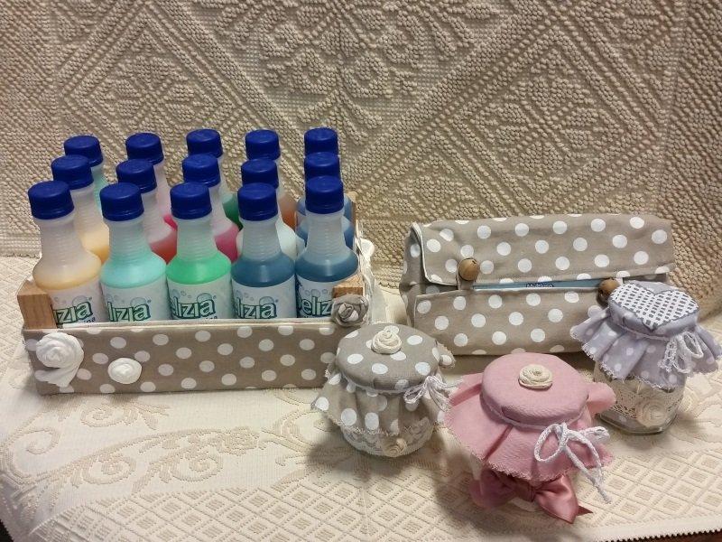 Cassa con bottiglie di liquido di colori , portatrucchi e tre vasetti di vetro con colori diversi