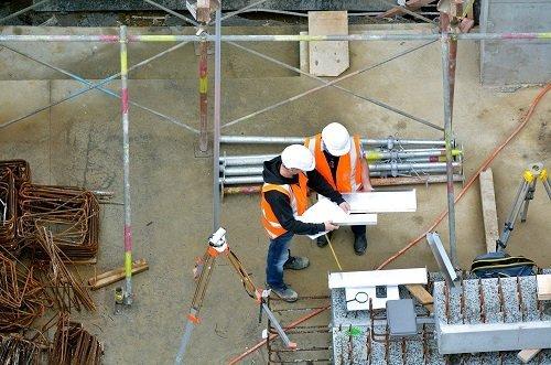 operai che controllano delle cartine di un cantiere