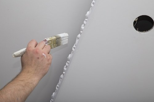 uomo pitturando un muro di bianco