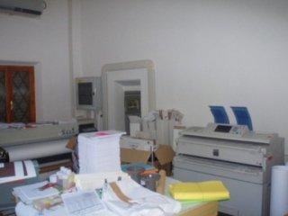 una stampante e una scrivania con dei volantini stampati