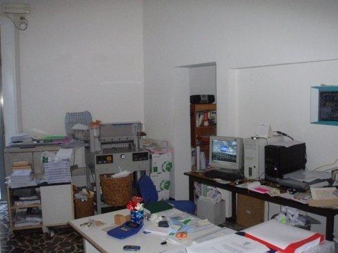 una scrivania un piccolo monitor e delle stampanti in un ufficio