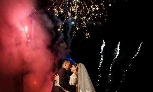 due sposi si baciano con i fuochi d'artificio sullo sfondo