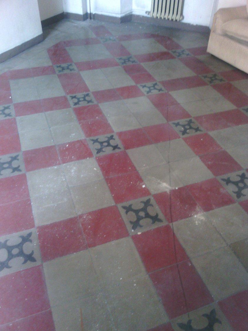 un pavimento con piastrelle  beige e rosse con dei disegni neri