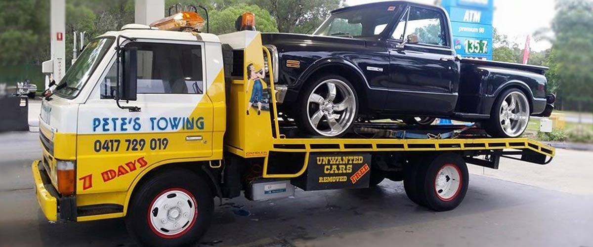 petes towing van towing black car
