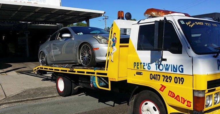 petes towing van towing a grey car