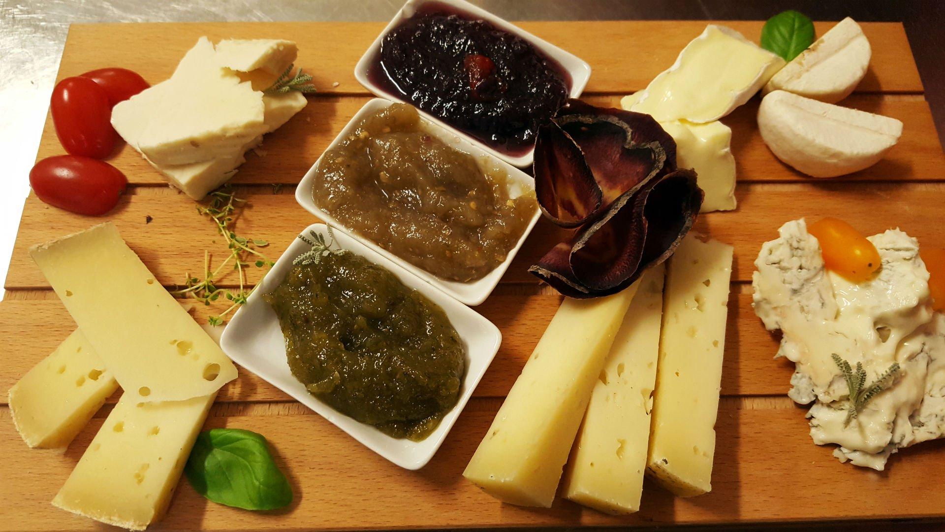 un tagliere con dei formaggi, pomodorini e delle salse
