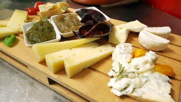 un tagliere dei formaggi e pomodorini gialli e rossi