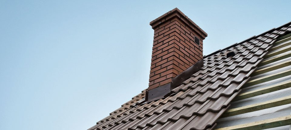 A chimney on a partly completed new roof