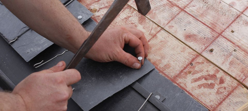 A man hammering grey slates onto a roof base
