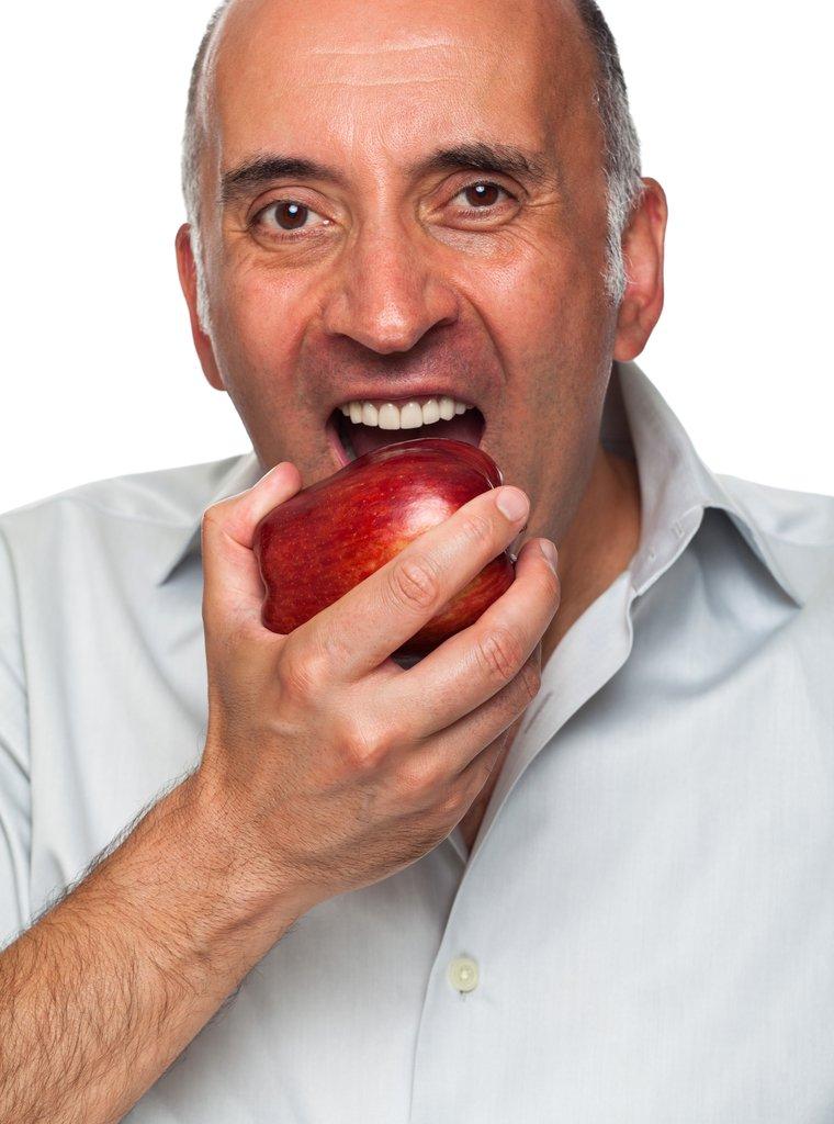 uomo mangia una mela