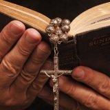 Mani di anziano con un libro aperto nelle mani del che pende un rosario