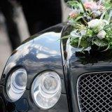fronte laterale destro del carro funebre con il cofano coperto di fiori bianchi
