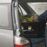 Mettendo fiori gialli sulla bara all'interno del carro funebre