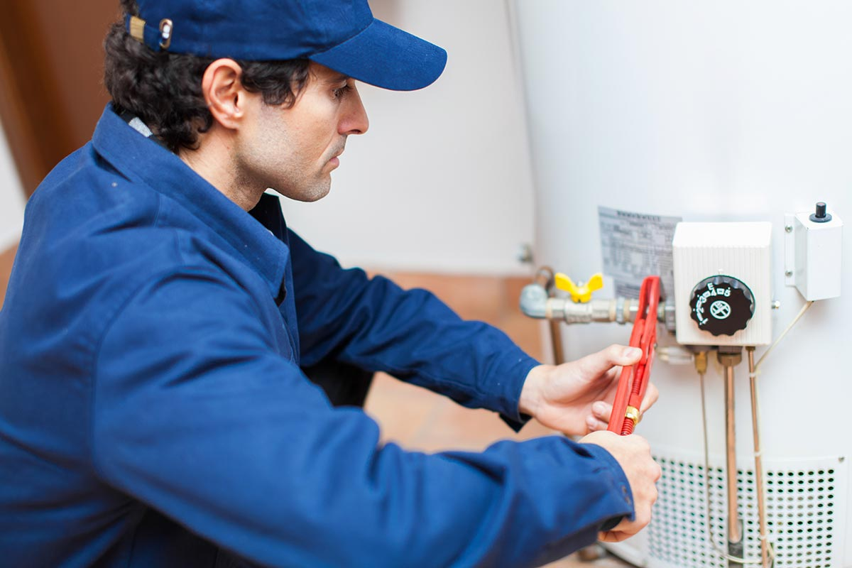 plumber in blue shirt working on a hot water system