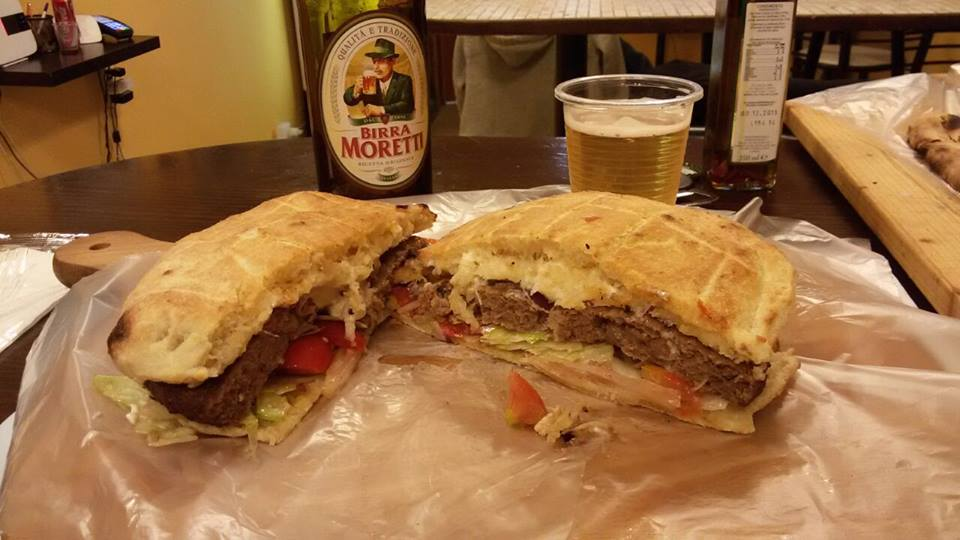 un panino tagliato a metà con carne, formaggio e verdure