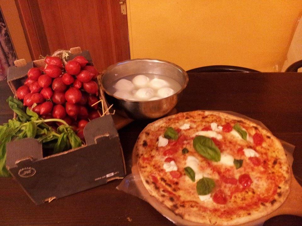 una cassa con dei pomodori,una bacinella delle mozzarelle e una pizza