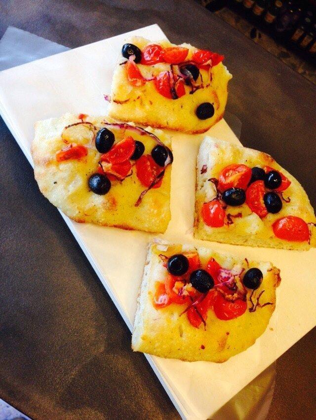 una focaccia con olive nere e pomodorini