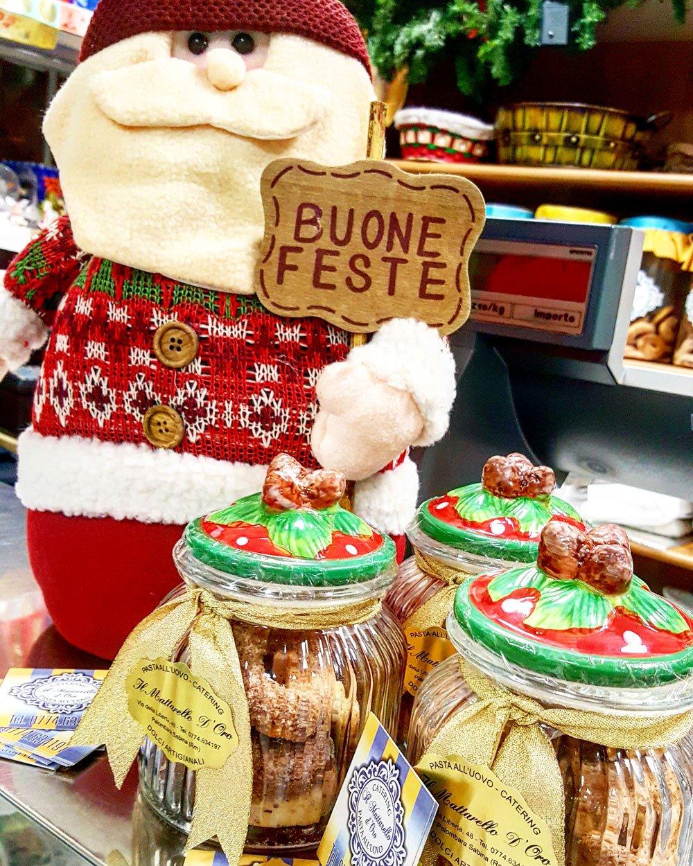 Babbo Natale di peluche con scritta Buone Feste e dolci nei barattoli