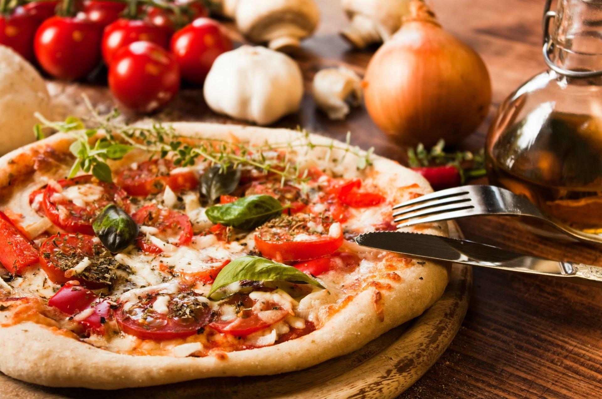 Pizza di pomodori freschi, mozzarella, aglio e rucola